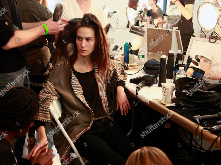 Stock Photo of Stylists do hair and nails for Mijo Mihaljcic, of Serbia, backstage before modeling the EDUN Spring 2014 collection during Fashion Week, in New York