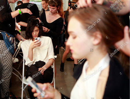 Chiharu Okunugi, from Japan, left, and Maddison Brown, from Sydney, foreground, use their phones as they have their hair done backstage before modeling the EDUN Spring 2014 collection during Fashion Week, in New York