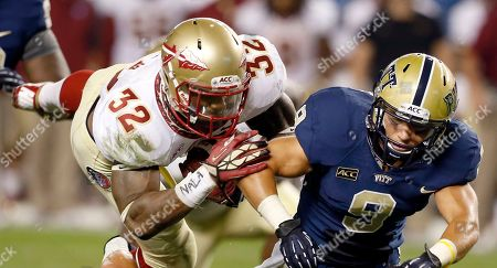Florida State running back James Wilder (32) dives over Pittsburgh towards linebacker Todd Thomas (8) in the second quarter of the NCAA college football game, in Pittsburgh