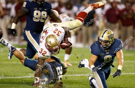 James Wilder, Anthony Gonzalez, Todd Thomas Florida State running back James Wilder (32) tumbles over Pittsburgh linebacker Anthony Gonzalez (28) as linebacker Todd Thomas (8) pursues in the second quarter of the NCAA college football game, in Pittsburgh
