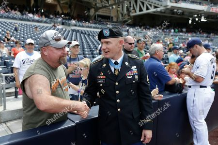 Stock Photo of Medal of Honor recipient Army Staff Sergeant Ty Michael Carter, right, shakes hands with Jeff Chase of Fort Sill, Okla., as he waits to throw out the ceremonial first pitch before the San Diego Padres play the San Francisco Giants, in San Diego. Carter was awarded the medal for conspicuous gallantry at the White House on Aug. 26. He's the fifth living military service member to receive the medal from the Afghanistan-Iraq era
