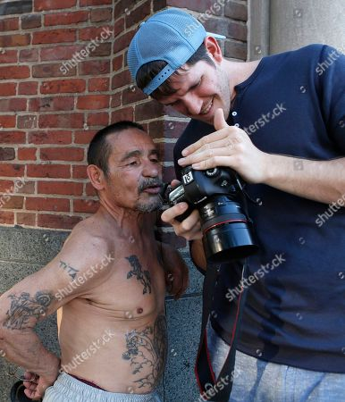 """Brandon Stanton This photo shows photographer Brandon Stanton, right, creator of the Humans of New York blog, showing Luis Torres, 63, a portrait he just took while combing the streets for subjects for his daily blog posts in New York. Stanton's magical blend of portraits and poignant, pithy storytelling has earned HONY more than 2 million followers online. Now he's putting his work in a book, """"Humans of New York,"""" due out Oct. 15 from St. Martin's Press"""