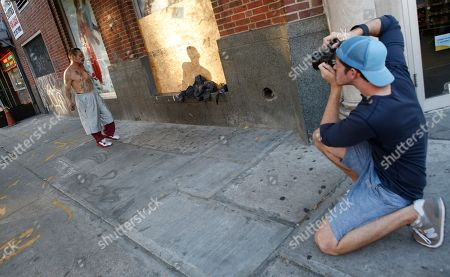 """Brandon Stanton This photo shows photographer Brandon Stanton, right, creator of the Humans of New York blog, as he takes a portrait of a dancing Luis Torres, 63, in the East Village in New York. Stanton's magical blend of portraits and poignant, pithy storytelling has earned HONY more than 2 million followers online. Now he's putting his work in a book, """"Humans of New York,"""" due out Oct. 15 from St. Martin's Press"""