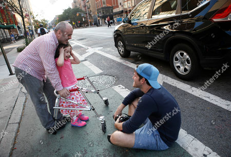 """Brandon Stanton This photo shows photographer Brandon Stanton, creator of the Humans of New York blog, right, after snapping a portrait of Mecit Kabatas and his five year-old daughter Bayza in New York. Stanton's magical blend of portraits and poignant, pithy storytelling has earned HONY more than 2 million followers online. Now he's putting his work in a book, """"Humans of New York,"""" due out Oct. 15 from St. Martin's Press"""