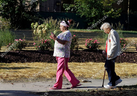 Carmen Gonzalez, left, and Maria Diaz walk past the site of the former home of Ariel Castro in Cleveland, on . Castro, 53, serving a life sentence for the kidnapping and rape of three women, was found hanging in his cell Tuesday night, Sept. 3, 2013, at the Correctional Reception Center in Orient, Ohio