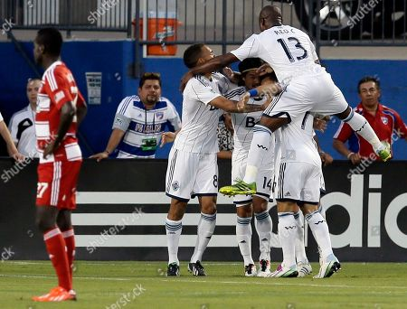 Je Vaughn Watson, Daigo Kobayashi, Nigel Reo-Coker Vancouver Whitecaps' Nigel Reo-Coker (13) celebrates with Daigo Kobayashi (14) and others after Kobayashi scored against FC Dallas in the first half of an MLS soccer game, in Frisco, Texas. FC Dallas' Je-Vaughn Watson stands in the left front
