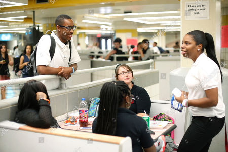 Stock Picture of Student Quentin Cooper, 18, left, speaks with friends during lunch on the first day of school at South Philadelphia High School, in Philadelphia. About 190,000 students are going back to class Monday in Philadelphia, where parents say severe staffing cuts have created an aura of uncertainty around the new academic year. Officials contend the school district is prepared despite the major budget reductions
