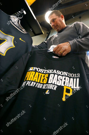 """Stock Image of Chris McLaughlin Chris McLaughlin holds on to some T-shirts he bought for his kids as he looks over other Pittsburgh Pirates shirts in the team's store at PNC Park, in Pittsburgh. McLaughlin says he has been a """"Bucco fan"""" since he was a kid, and was buying the shirts for his children because they asked him to after the Pirates clinched a spot in the playoffs the night before"""