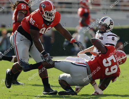 Georgia linebacker Jordan Jenkins (59) pulls down South Carolina quarterback Connor Shaw (14) as Georgia nose tackle Mike Thornton (96) looks on during the first half of an NCAA football game, in Athens, Ga