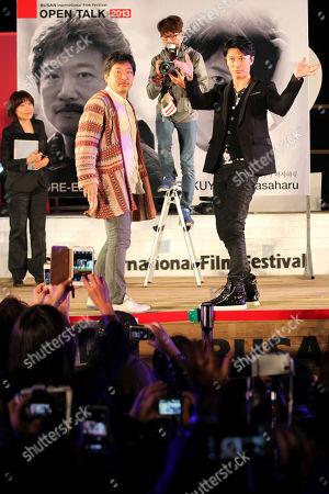 Japanese director Hirokazu Koreeda, second left, and actor Masaharu Fukuyama pose on the stage during Busan International Film Festival at BIFF Village on Haeundae beach in Busan, south of Seoul, South Korea
