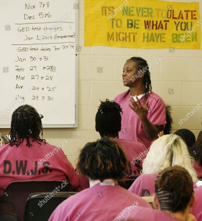 "Sheila Johnson, 33, addresses other inmates during a meeting of Prostitution Anonymous at the Cook County Jail in Chicago, on . Johnson told her peers how she had a difficult time breaking free from a boyfriend who was also her pimp. She was addicted to drugs - and, she admitted, ""the money."" ""As a regular person, I wouldn't dare do the things that I did because I was on drugs,"" she said after the meeting, as tears streamed down her face. ""Being sober, I wouldn't DARE prostitute"