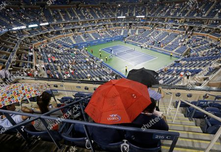 Patrons huddle under an umbrella during a rain delay in the opening round of the U.S. Open tennis tournament, in New York. The match between Switzerland's Roger Federer and Slovenia's Grega Zemlja was postponed due to rain