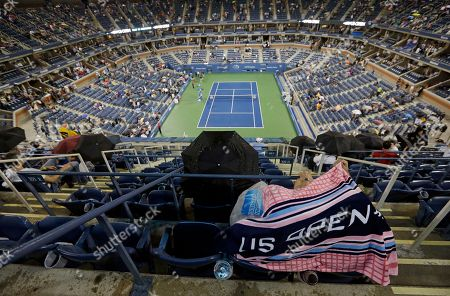 Patrons huddle under a towel during a rain delay in the opening round of the U.S. Open tennis tournament, in New York. The match between Switzerland's Roger Federer and Slovenia's Grega Zemlja was postponed due to rain
