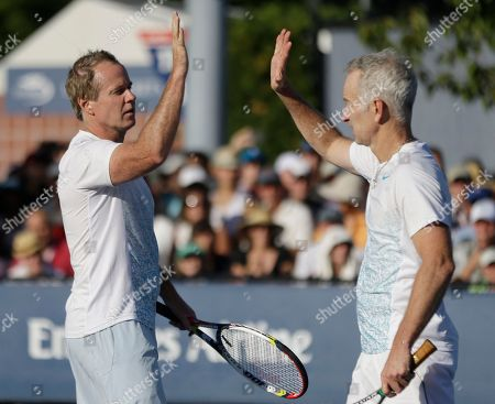 John McEnroe, Patrick McEnroe John McEnroe high fives his brother Patrick McEnroe during an exhibition doubles match against Cedric Pioline, of France, and Mats Wilander, of Sweden, at the 2013 U.S. Open tennis tournament, in New York