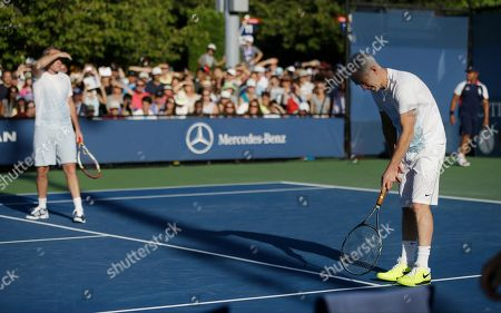 John McEnroe John McEnroe, right, questions a call on the line by the umpire as his brother Patrick McEnroe looks on during an exhibition doubles match against Cedric Pioline, of France, and Mats Wilander, of Sweden, at the 2013 U.S. Open tennis tournament, in New York