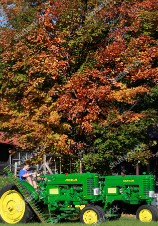 Sam Frost checks out an antique tractor at the Morse Farm Sugarworks under a bright fall foliage on in East Montpelier, Vt. Many places in Vermont are approaching peak foliage season