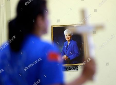 A portrait of former Texas Gov. Ann Richards is displayed as an anti-abortion demonstrator holds a cross in the rotunda of the Texas Capitol, in Austin, Texas. The fight over access to abortion in Texas resumed Monday, with a Senate hearing and a nighttime anti-abortion rally at the Capitol
