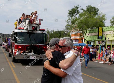 Stock Picture of Don Devendorf, Peter Gordon Prescott Fire Marshal Don Devendorf, right, is hugged by Chief Peter Gordon as a fire truck carrying friends and family members of Granite Mountain Interagency Hotshot Crew rides in Prescott Frontier Days Rodeo Parade in Prescott, Ariz. The firefighters were killed battling a wildfire near Yarnell, Ariz., Sunday, June 30