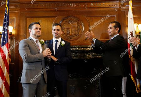 """Jeff Zarrillo, Paul Katami, Antonio Villaraigosa Los Angeles Mayor Antonio Villraigos, right, applauds after he married Jeff Zarrillo, left, and Paul Katami at City Hall in Los Angeles. A three-judge panel of the 9th U.S. Circuit Court of Appeals issued a brief order Friday afternoon dissolving, """"effective immediately,"""" a stay it imposed on gay marriages while the lawsuit challenging the ban advanced through the courts"""
