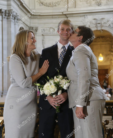Sandy Stier, Kris Perry, Elliott Perry Elliott Perry, center, is kissed by his mother, Kris Perry, after his parents, Sandy Stier, left, and Perry were wed by California Attorney General Kamala Harris at City Hall in San Francisco, . Stier and Perry, the lead plaintiffs in the U.S. Supreme Court case that overturned California's same-sex marriage ban, tied the knot about an hour after a federal appeals court freed same-sex couples to obtain marriage licenses for the first time in 4 1/2 years