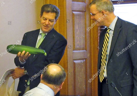 Kansas Gov. Sam Brownback, left, brings zucchini squash from the garden of his family's Topeka home to a meeting with legislative leaders, including Senate Minority Leader Anthony Hensley, seated, and House Minority Leader Paul Davis, right, at the Statehouse in Topeka, Kan. Brownback gave away most of the squash to Senate Ways and Means Committee Chairman Ty Masterson