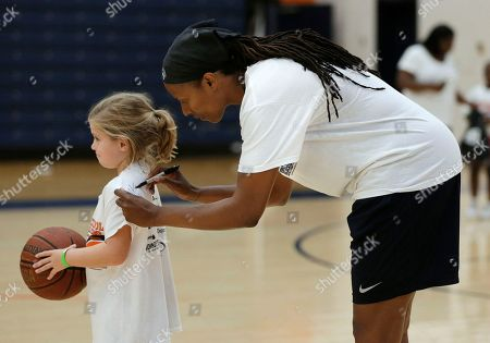 """Chamique Holdsclaw, Lily Maggart Former WNBA star and Olympic gold medalist Chamique Holdsclaw autographs the shirt of Lily Maggart, 7, after a youth basketball clinic, in Hendersonville, Tenn. Holdsclaw said she's getting her life back in order after a few months that felt like a """"mental prison"""" after an arrest last November"""