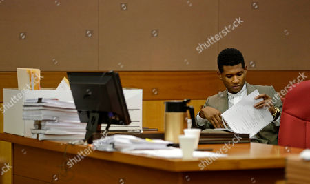 Usher R&B singer Usher reads through documents while waiting for a child custody hearing to begin, in Atlanta. A judge in Atlanta is set to hear arguments in the child custody battle between Usher and his ex-wife. Tameka Foster Raymond requested the hearing earlier this week after the former couple's son got caught in a pool drain while in the care of the Grammy winner's aunt