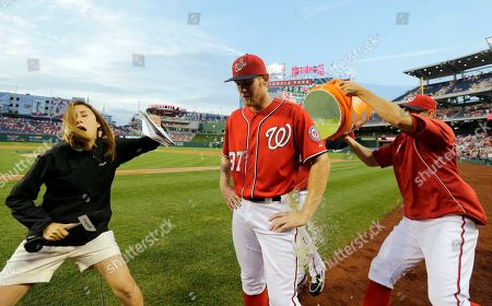 Stephen Strasburg, Craig Stammen, Julie Alexandria, Tyler Clippard As MASN's Julie Alexandria interviews Washington Nationals starting pitcher Stephen Strasburg (37), teammates Tyler Clippard, and Craig Stammen, right, prepare to douse Strasburg with Gatorade, after a baseball game against the Philadelphia Phillies at Nationals Park, in Washington. Strasburg pitched his first complete game, and the Nationals won 6-0