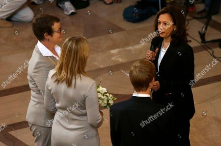Attorney General Kamala Harris, right, officiates the wedding of Kris Perry, left, and Sandy Stier, second from left, in San Francisco, . Stier and Perry were married Friday, June 28, 2013, after a federal appeals court on Friday cleared the way for the state of California to immediately resume issuing marriage licenses to same-sex couples after a 4 1/2-year freeze