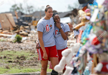 Elizabeth Cambage, Glory Johnson WNBA Tulsa Shock's Elizabeth Cambage, left, and Glory Johnson, right, embrace as they look at a memorial to the seven students who died at Plaza Towers Elementary school during Moore's tornado, at the site of the school, in Moore, Okla., . The Shock held a basketball clinic for students impacted by the tornado and later toured the site