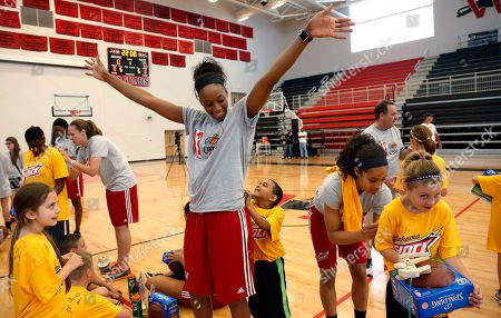 Glory Johnson, Damian Moore, Skylar Diggins, Abigail Cowell WNBA's Glory Johnson, left center, holds her arms high as Damian Moore, right center, autographs her shirt during a basketball clinic for schoolchildren impacted by the tornado, in Moore, Okla. Skylar Diggins, right, signs the shirt of Abigail Cowell