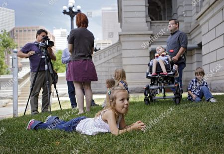 Cory Mathis, Kathryn Mathis, Jeremy Mathis Coy Mathis, 6, lays in the grass at the Capitol as her mother Kathryn Mathis does a television interview in the background in Denver on . Her father Jeremy and brother and sisters are also pictured. The Colorado Civil Rights Division has ruled in favor of six-year-old Coy Mathis, whose school had barred her from using the girls' bathroom at her elementary school because she is transgender