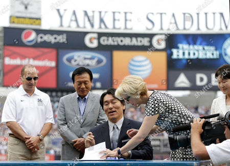 Stock Image of Brian Cashman, Masao Matsui, Hideki Matsui, Jean Afterman, Saeko Matsui New York Yankees general manager Brian Cashman, left, watches as Yankees assistant general manager Jean Afterman, second from right, signs paperwork with the Yankees 2009 World Series MVP Hideki Matsui, center, during Matsui's retirement ceremony aft home plate before the Yankees 55th baseball game of the year, in New York. Matsui's father Masao, second from left, and mother Saeko, far right, watch the ceremony