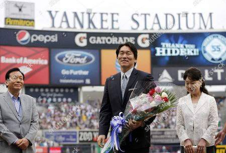 Stock Picture of Masao Matsui, Hideki Matsui, Saeko Matsui 2009 World Series MVP Hideki Matsui, center, who wore the number 55 as a member of the New York Yankees, is flanked by his father Masao, left, and mother Saeko, as he is honored prior to his official retirement ceremony before the Yankees 55th baseball game of the year, in New York