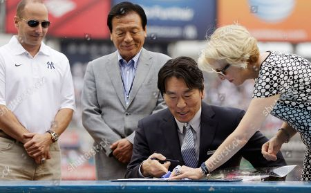 Brian Cashman, Masao Matsui, Hideki Matsui, Jean Afterman New York Yankees General Manager Brian Cashman, left, watches as Yankees Assistant general manager Jean Afterman, right, shows 2009 World Series MVP Hideki Matsui, center, where to sign his retirement papers during Matsui's retirement ceremony prior to the Yankees 55th baseball game of the year, in New York. Matsui's father Masao, second from left, looks over Matsui's shoulder during the process