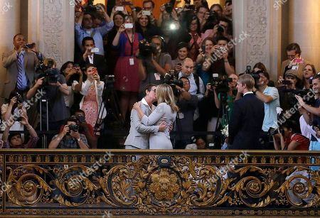 FOR USE AS DESIRED, YEAR END PHOTOS - FILE - Kris Perry, foreground left, kisses Sandy Stier as they are married at City Hall in San Francisco, . Stier and Perry were married after a federal appeals court cleared the way for the state of California to immediately resume issuing marriage licenses to same-sex couples after a 4 1/2-year freeze