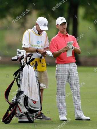 Guan Tianlang Amateur Guan Tianlang, 14, of China talks with his caddie, Bob Swanson, on the 10th fairway during the first round of the Byron Nelson Championship golf tournament, in Irving, Texas. Tianglang finished the round at even par