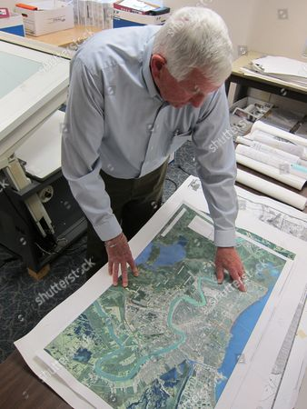 """John Sayles Shows John Sayles, 79, a planner at Stanley Consultants, reviewing a map from a New Orleans project he worked, at the company's headquarters in Muscatine, Iowa. Sayles is among the employees at Stanley who have participated in """"phased retirement,"""" in which a worker can cut back their hours in the months or years before their formal retirement, and continue to work part-time after. Employers around the country offer phased retirement, giving older workers a chance to transition more slowly to their post-career life"""
