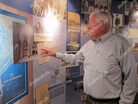 """In this, photo John Sayles, a planner at Stanley Consultants, gestures at a display of the company's history at its headquarters in Muscatine, Iowa. Sayles, 79, is among the employees at Stanley who have participated in """"phased retirement,"""" in which a worker can cut back their hours in the months or years before their formal retirement, and continue to work part-time after. Employers around the country offer phased retirement, giving older workers a chance to transition more slowly to their post-career life"""