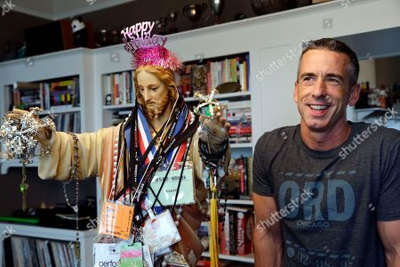 Stock Picture of Dan Savage Author Dan Savage stands with a three-foot tall statue of Jesus, adorned with old press credentials, rosaries, beads and other miscellaneous items, in his home in Seattle