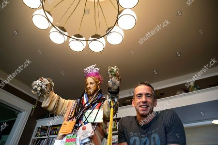 Dan Savage Author Dan Savage poses with a three-foot tall statue of Jesus, adorned with old press credentials, rosaries, beads and other miscellaneous items, in his home in Seattle