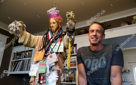 "Stock Photo of Dan Savage On, author Dan Savage stands with a three-foot tall statue of Jesus, adorned with old press credentials, rosaries, beads and other miscellaneous items, in his home in Seattle. Savage's latest book, ""American Savage,"" was released on Tuesday, May 28"
