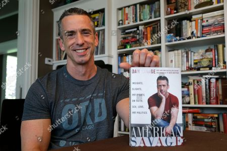 "Dan Savage On, author Dan Savage holds his new book, ""American Savage,"" as he sits in his home in Seattle. Savage's latest book, ""American Savage,"" was released on Tuesday, May 28"