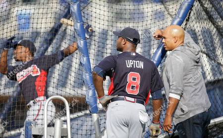 Stock Picture of David Justice, B.J. Upton, Justin Upton Atlanta Braves' Justin Upton and former Braves' player David Justice watch as Upton's brother, B.J. Upton, hits in the batting cage during warmups prior to a baseball game in San Diego