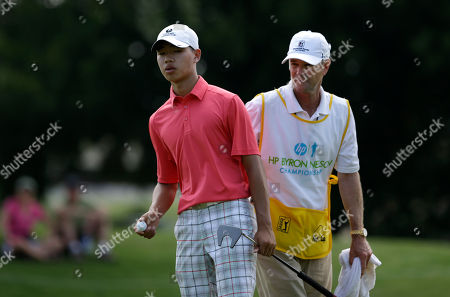 Guan Tianglang Amateur Guan Tianlang, 14, of China talks with his caddie during the first round of the Byron Nelson Championship golf tournament, in Irving, Texas. Tianglang finished even on the first day