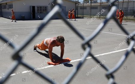 Inmate Kevin Barry does pushups in the exercise yard of Sacramento County's Rio Cosumnes Correctional Center in Elk Grove, Calif., . A report by the California Little Hoover Commission says Gov. Jerry Brown's prison realignment plan is forcing county sheriff's rather than judges, to decide which inmates get released early from jail and which serve their full sentences
