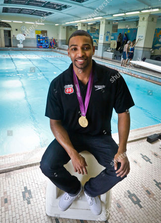 """This photo shows Olympic gold medalist swimmer Cullen Jones posing poolside after giving swimming lesson's to students at Harlem's P.S. 125 in New York. Jones is ambassador for the 5th Annual USA Swimming Foundation's """"Make a Splash Tour,"""" a program to provide free swimming lessons, water safety education and awareness at city pools"""