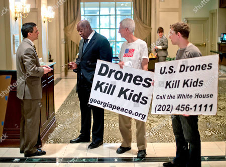 Joe Beasley, Bob Goodman, Kevin Caron Civil rights activist Joe Beasley, second from left, and activists Bob Goodman and Kevin Caron, right, speak with a Grand Hyatt Hotel employee, left, while attempting to enter the International Conference on Unmanned Aircraft Systems taking place in a nearby ballroom as they protest the use of drones, in Atlanta. Conference organizers say the gathering allows representatives from academia, industry and government to discuss expansion of unmanned aerial vehicles commonly called drones