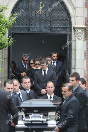 Andrea Rebello's father Fernando, left, twin sister Jessica, second from left and mother Nella, third from left, follow Rebello's casket after her funeral service at St. Teresa of Avila Church in Sleepy Hollow, N.Y. A Long Island district attorney has decided not to prosecute a police officer who killed the Hofstra University student and the armed intruder who was holding her hostage. Nassau County District Attorney Kathleen Rice issued a 28-page report, stating that a prosecution of Police Officer Nikolas Budlimic is not warranted. Budlimic fired at the intruder who was holding Rebello in a headlock when he was the first officer to arrive at the report of a home invasion in 2013. One round missed the intruder but struck and killed Rebello by mistake