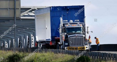 """A dented upper corner and a scrape along the upper side are visible on the """"oversize load""""equipment casing being hauled a truck parked southbound as a pair of Washington State Patrol troopers stand nearby on Interstate 5 south of the collapsed portion of the highway bridge at the Skagit River, in Mount Vernon, Wash. The truck struck the four-lane bridge on the major thoroughfare between Seattle and Canada Thursday evening, sending a section of the span and two vehicles into the Skagit River. All three occupants suffered only minor injuries. At an overnight news conference, Washington State Patrol Chief John Batiste blamed the collapse on a tractor-trailer carrying a tall load that hit an upper part of the span"""